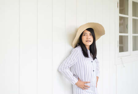 Portrait of beautiful asian woman wearing hat and standing at home,Positive thinking,Good attitude