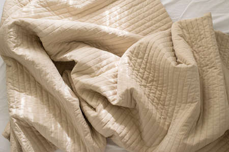 Crumpled blanket with sunlight on bed after wake up in the morning,Brown color toned,Top view