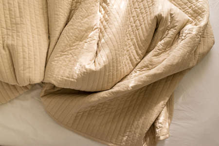 Crumpled blanket with sunlight on bed after wake up in the morning,Brown color toned
