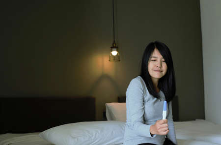 Beautiful asian woman hand showing pregnancy test after testing  in her bedroom,Happy and smiling Reklamní fotografie