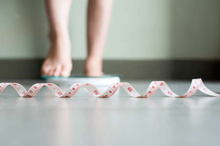 Blured of women foot standing on weigh scales with tape measure in foreground Reklamní fotografie