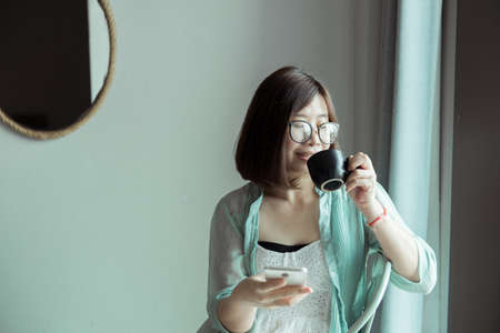 Portrait of beautiful asian woman is holding a cup of coffee and looking something on window at home in the morning,Happy and smiling Reklamní fotografie