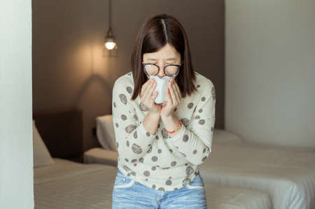 Asian woman sneeze because pollution in bedroom,Young female got nose allergy Reklamní fotografie