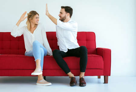 Couple lover hand clapping feeling happy and sitting on sofa at home,Cheerful and attractive people