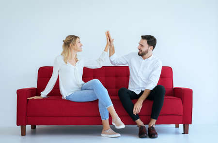 Couple lover hand clapping feeling happy and sitting on sofa at house,Cheerful and attractive people Reklamní fotografie
