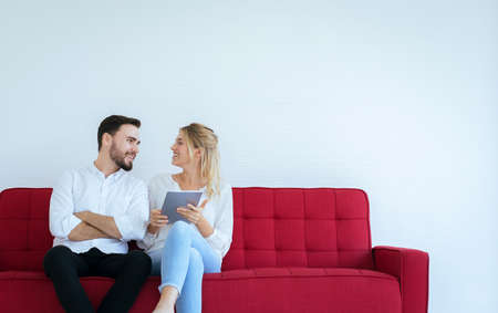 Couple relaxing on a sofa and using tablet at home together,Happy and smiling,Free time