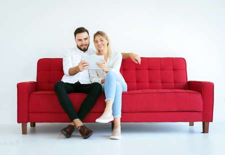 Couple relaxing on a sofa and looking movie online with tablet at home together,Happy and smiling,Free time concept Reklamní fotografie