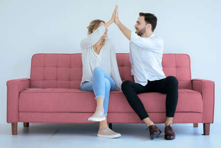 Couple lover hands clapping feeling happy and sitting on sofa at home,Cheerful and attractive people Reklamní fotografie