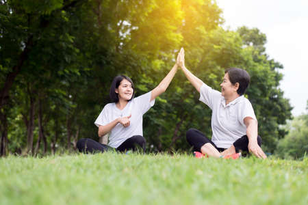 Healthy and lifestyle concept,Asian woman raise up hands and relax at public park in the morning together,Happiness and smiling,Positive thinking