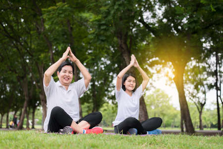 Beautiful asian woman practicing yoga at public park in the morning,Happy and smiling,Positive thinking,Healthy and lifestyle concept
