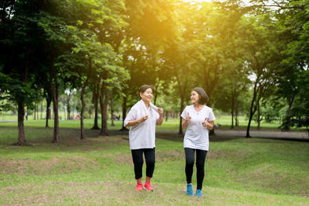 Portrait of elderly asian woman with daughter running in the park in early morning together,Healthy and Take care concept