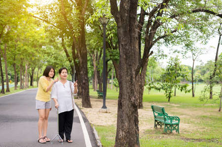 Portrait of a elderly asian woman with young female pointing something at outdoor together in the morning,Positive thinking