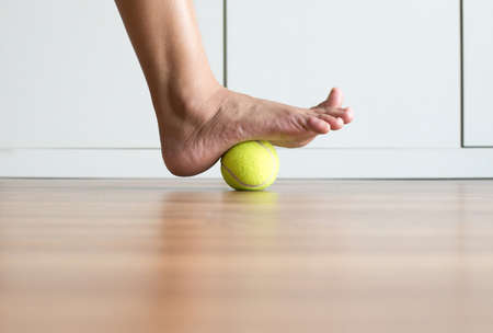 Woman massage with tennis ball to her foot in bedroom