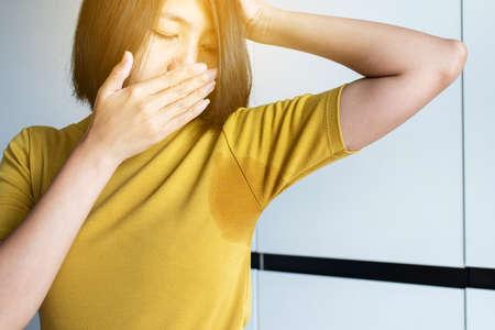Asiatische Frau mit Schwitzen, Frau, die ihre Achsel riecht oder schnüffelt, schlechtes Geruchskonzept mit Kopienraum für Text und weißem Hintergrund