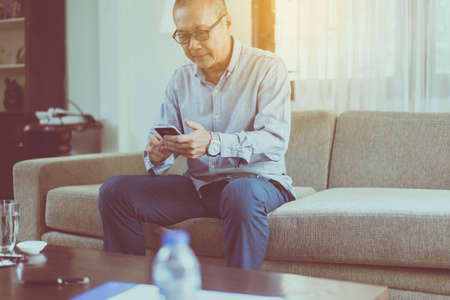 Senior asian man having rest and using smartphone connecting internet at home, Relaxing time, Happy and smiling