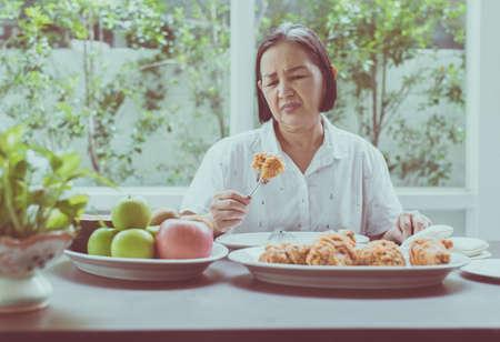 Donna asiatica anziana che si sente pasto infelice e annoiato, concetto di salute anziana Archivio Fotografico
