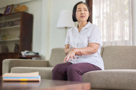 Senior asian woman suffering with parkinson's disease symptoms on hands Stock Photo