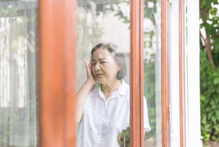 Senior healthy concept, Mature asian elderly woman having migraine and headache pain near window at home Foto de archivo