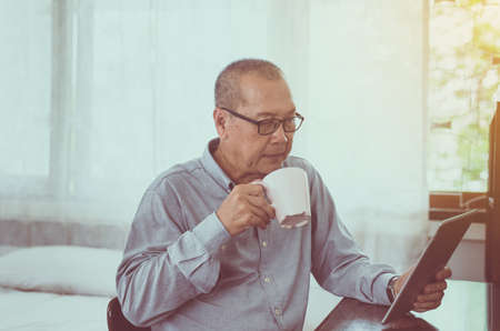 Asian senior man relaxing drinking coffee and using digital tablet at home in the morning