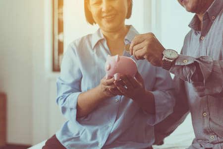 Senior aziatische paarhanden die munt in spaarvarken zetten voor pensioen samen, geld besparen concept Stockfoto