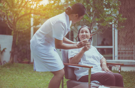Senior asian woman hands holding a glass of water with pills, Nursing home care concept