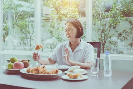 Senior asian woman feeling unhappy and bored meal, Elderly healthy concept