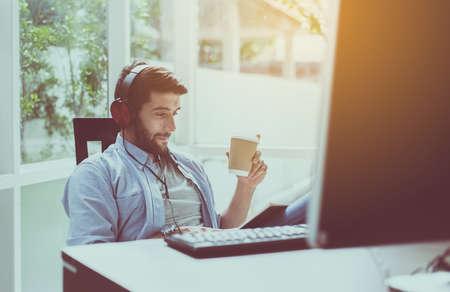 Portret van een knappe man met baard die hete koffie drinkt en online naar muziek luistert in een modern huis, gelukkig en glimlachend, ontspannen tijd Stockfoto