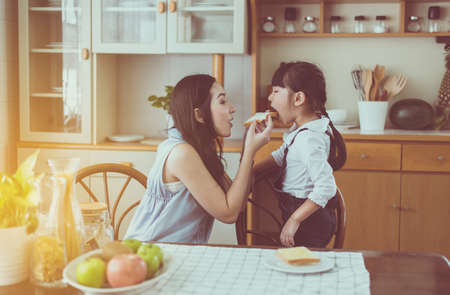 Single mother feeding bread to little daughter having fun with breakfast together at home kitchen in the morning Stock Photo