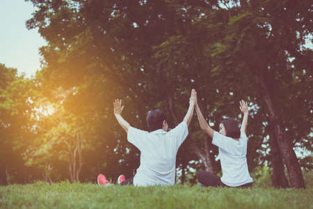 Asian women raise up hands and relax at park in the morning together,Happy and smiling,Positive thinking,Healthy and lifestyle concept Stock Photo