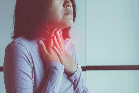 Frauen haben Halsschmerzen, Frauen, die ihren Hals mit den Händen berühren, Gesundheitskonzept Standard-Bild