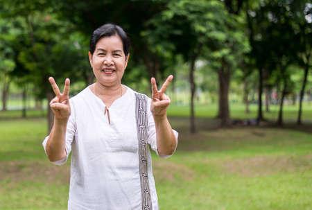 Ritratto di una donna asiatica anziana in piedi e che mostra la mano della pace canta al parco, faccia felice e sorridente Archivio Fotografico