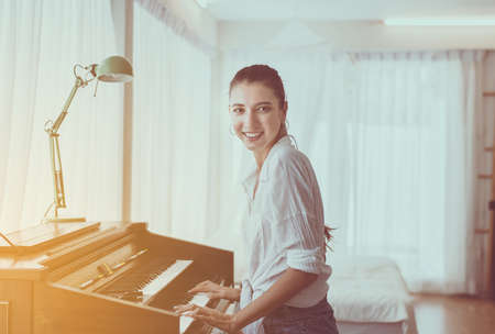 Beautiful young woman playing piano,Happy and smiling,Relaxing time