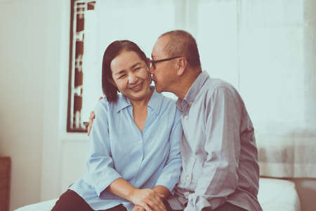 Happy couple senior asian kiss to cheek togeter on bed at home