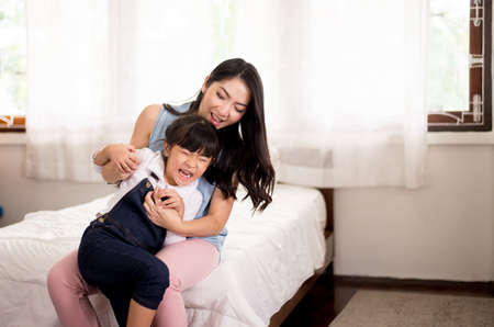 Asian single mom be easily incited and carrying her cheerful daughter at home,Happy and funny Stock fotó