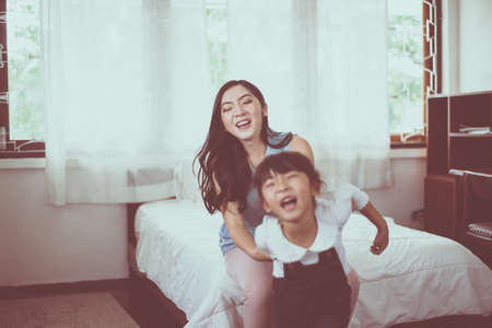 Asian single mom and carrying her cheerful daughter at home together,Happy and funny Stock fotó