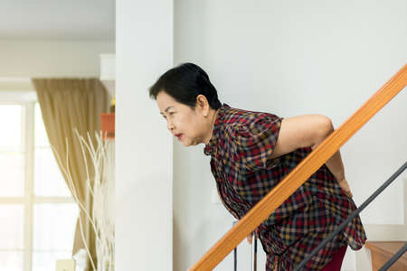 Asian senior older woman suffering from low-back lumbar pain while walking on stair at home