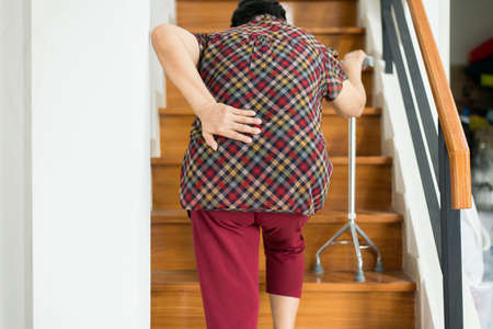 Asian elderly older woman suffering from low-back lumbar pain while walking on stair at home