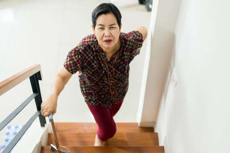 Asian senior older woman suffering from low-back lumbar pain while walking up on stair at home Stock Photo