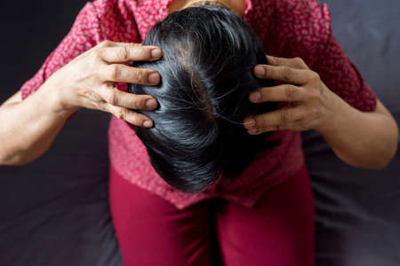 Woman showing black gray hair roots on her head,Close up,Top view