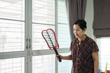 Middle aged woman using mosquito swatter at home,Female with mosquito electric net racket in living