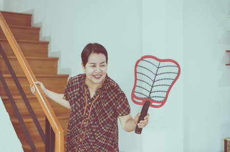 Female with mosquito electric net racket at house,Senior woman using mosquito swatter at home Zdjęcie Seryjne