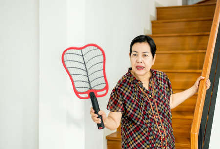 Elderly woman using mosquito swatter at home,Female with mosquito electric net racket