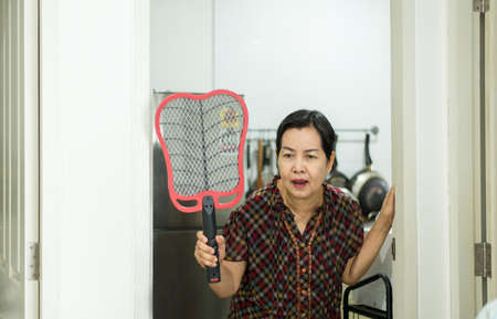 Senior woman using mosquito swatter at home,Female with mosquito electric net racket in bedroom