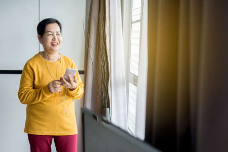 Senior asian woman listening to music with earphone,Elderly female using mobile phone feeling funny and enjoying,Relaxing time,Happy and smiling