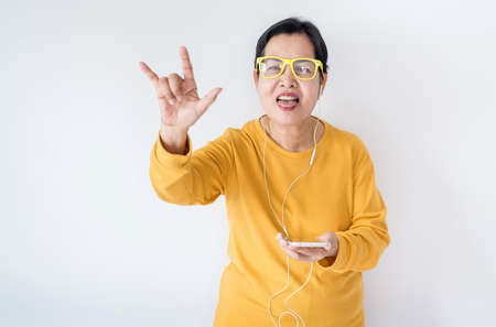 Senior asian woman listening to music with earphone,Elderly female using smartphone feeling funny and enjoying,Relaxing time,Happy and smiling Stok Fotoğraf