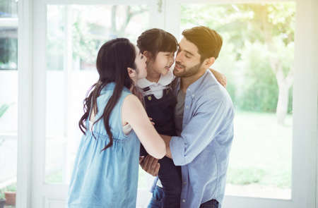Father and mother kiss cheek daughter child girl playing,Laughing and funny together at home,Happy loving family Stok Fotoğraf