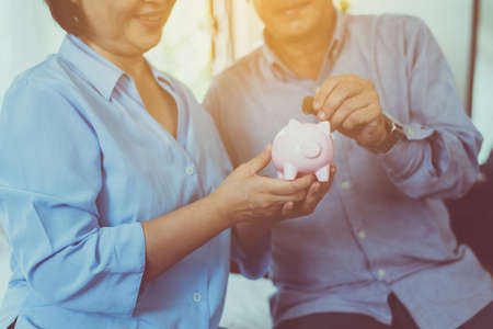 Senior couple hands putting coin to piggy bank for retirement together,Saving money concept
