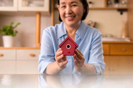 Senior hands holding home red color model for retirement,Saving money concept