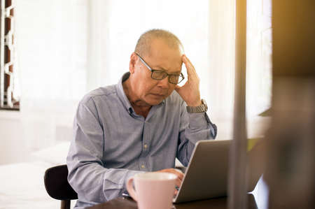 Senior asian elderly man having migraine and headache pain while working at home,Elderly healthy concept