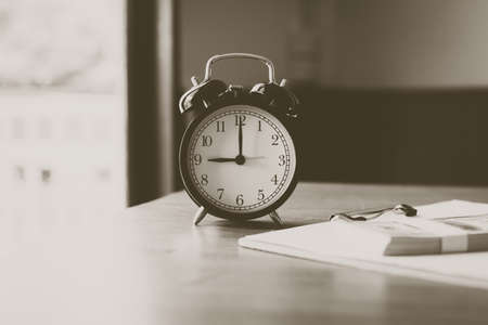 Close up of modern alarm clock at 9 oclock on desk in the moning,Black and white toned